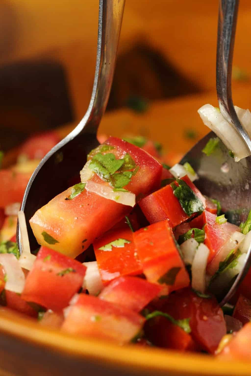 Pico de gallo in a wooden bowl with salad spoons.