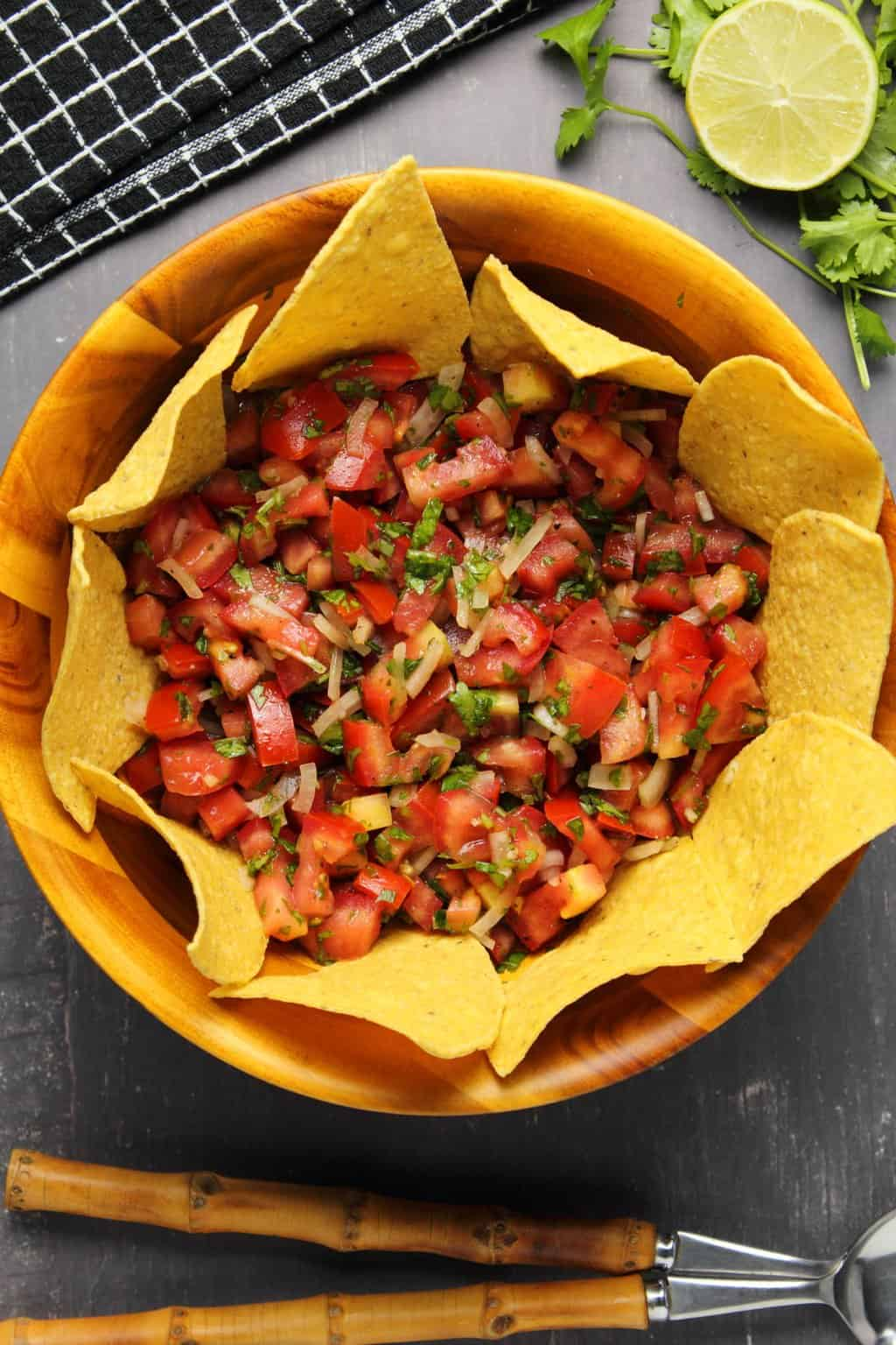 Pico de gallo in a wooden bowl surrounded by corn chips.