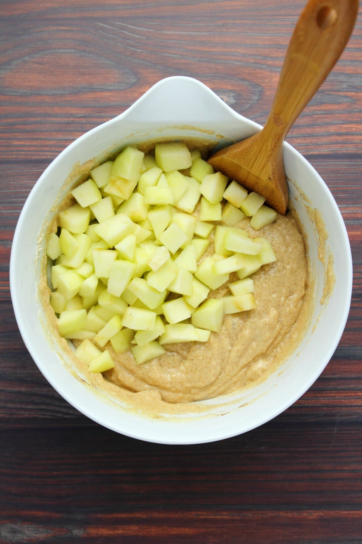 Chopped apple slices on top of vegan apple cake batter in a white mixing bowl.