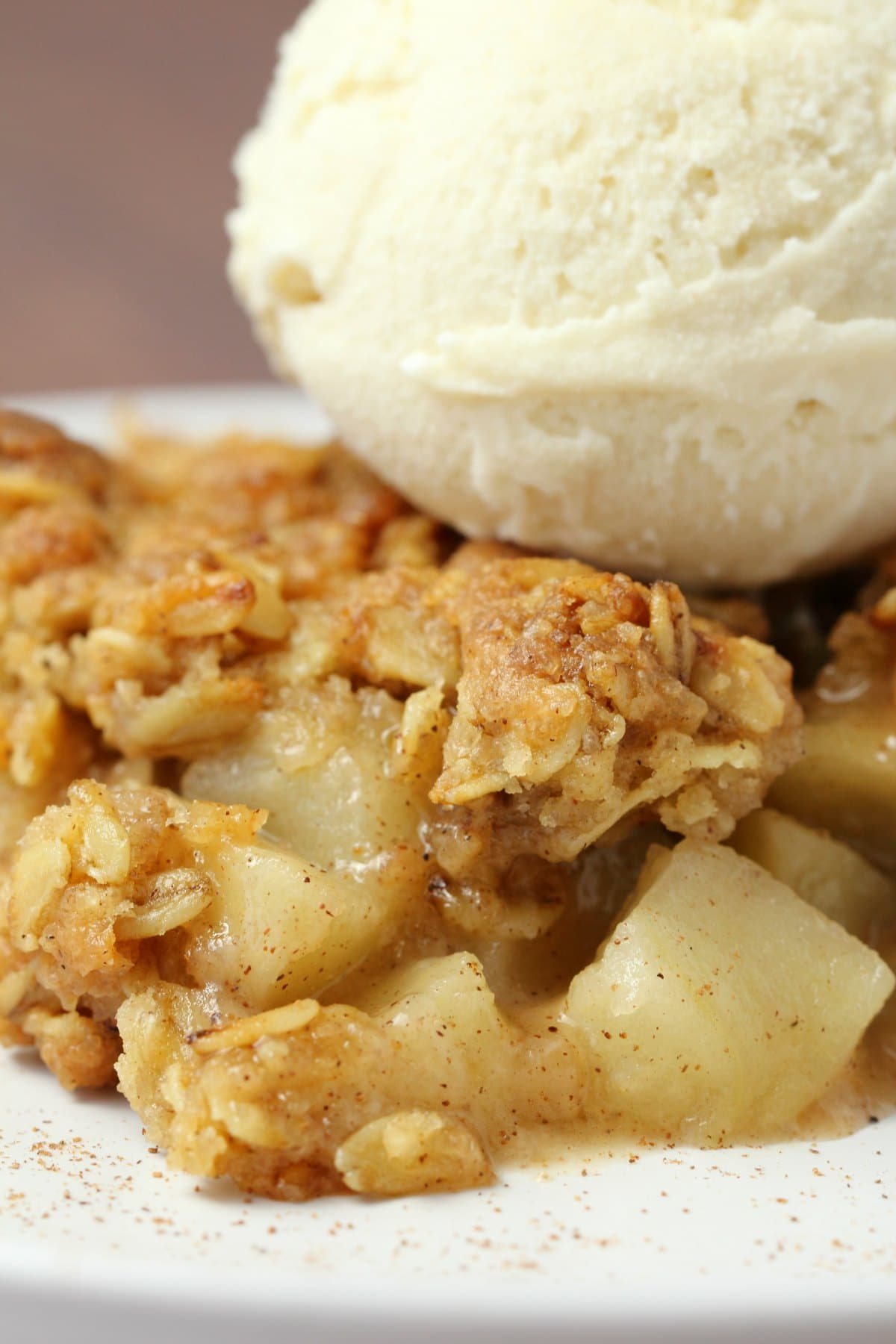 A slice of vegan apple crisp with a scoop of vegan vanilla ice cream on top.