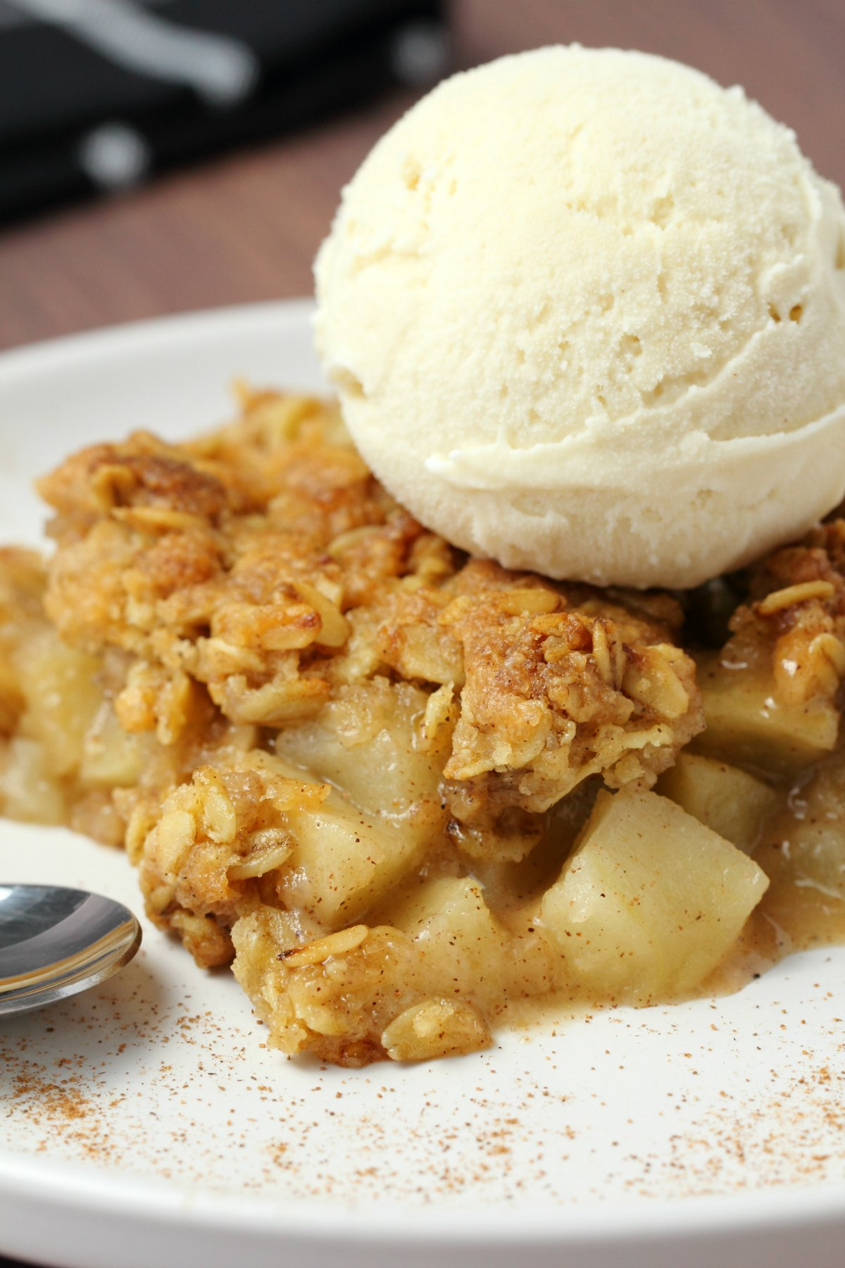 A slice of vegan apple crisp topped with vegan vanilla ice cream on a white plate.