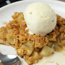 Slice of vegan apple crisp topped with a scoop of ice cream on a white plate.