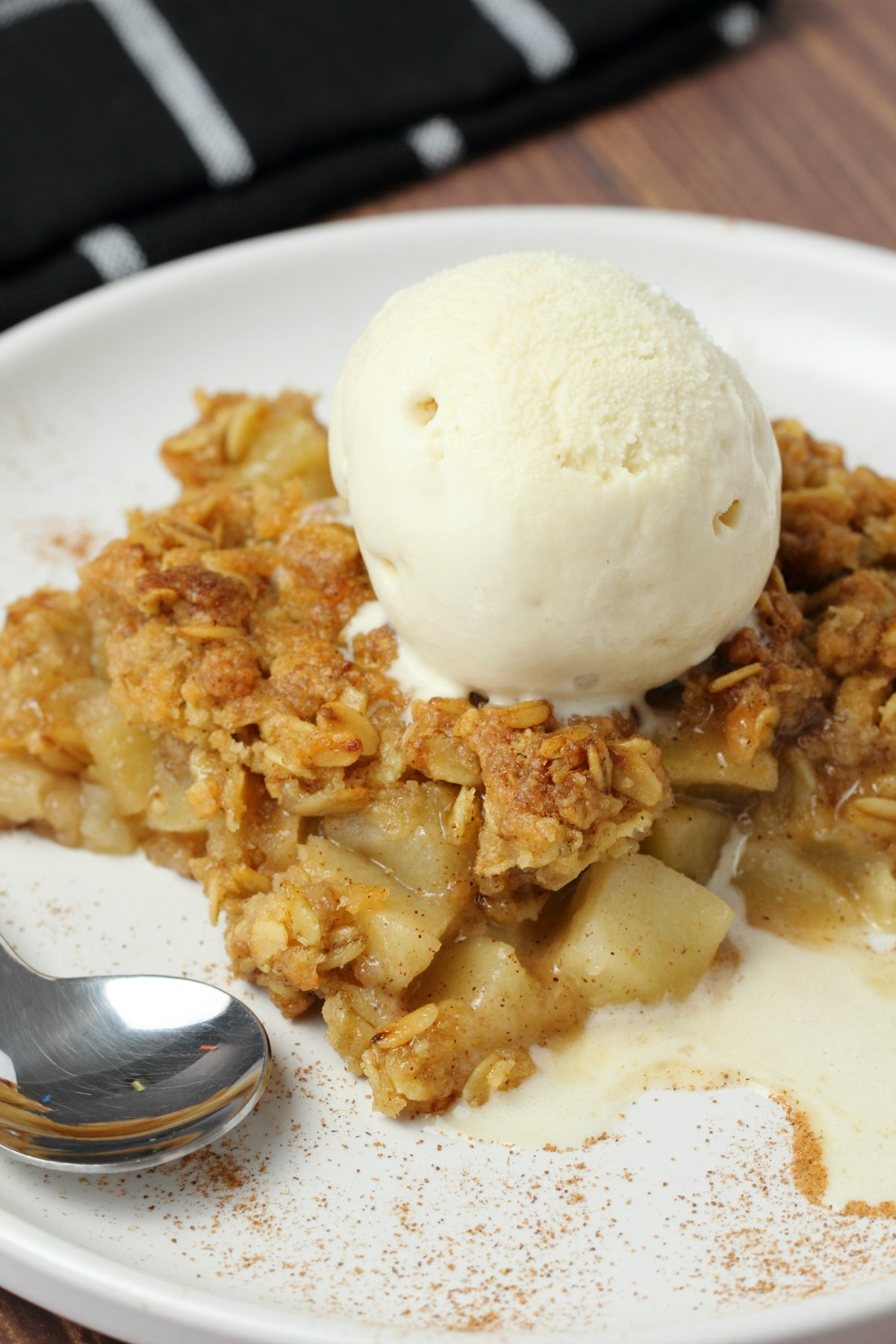 A slice of vegan apple crisp with a scoop of vegan vanilla ice cream on top on a white plate.