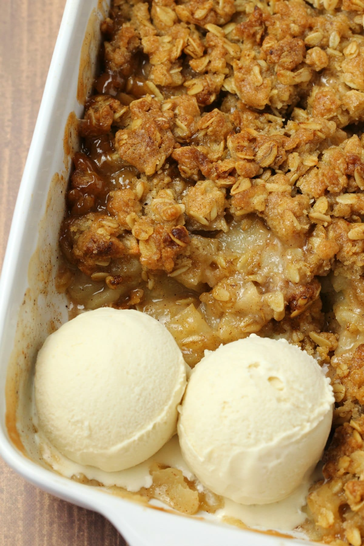 Vegan apple crisp in a white ceramic dish with two scoops of vegan vanilla ice cream.