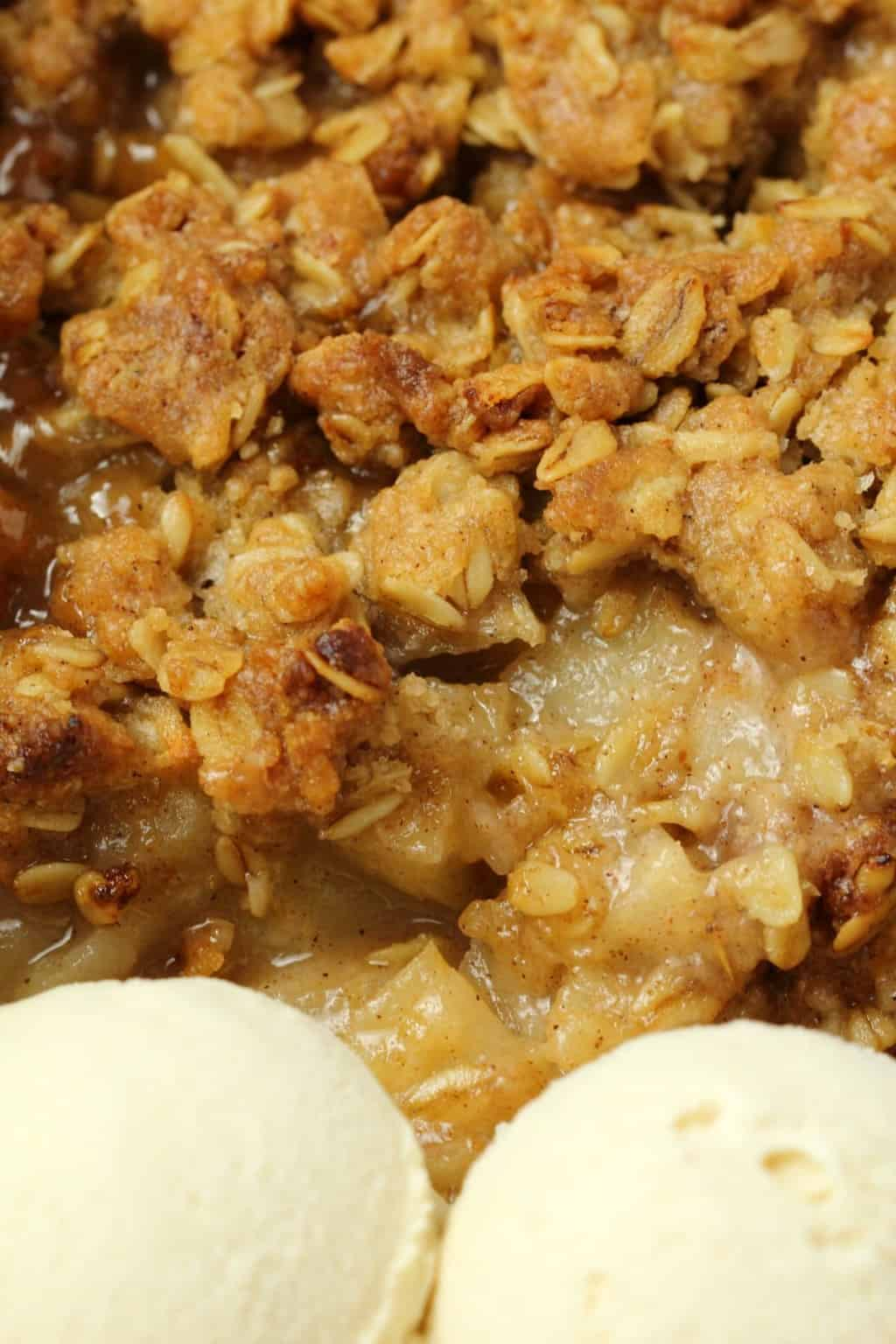 Vegan apple crisp with two scoops of vegan vanilla ice cream.