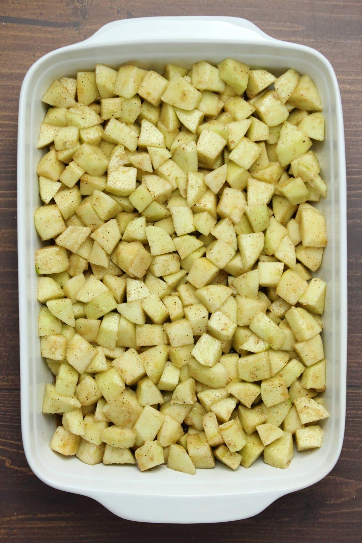 Chopped apple filling for apple crisp in a white rectangle baking dish.