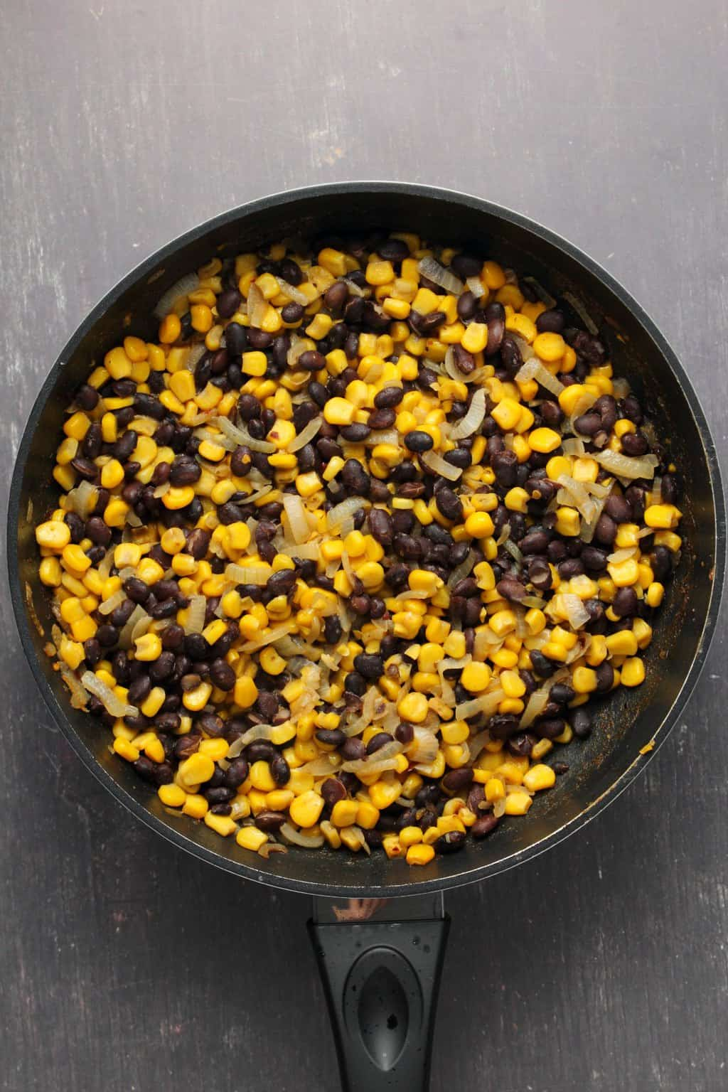 Black bean and corn mix for vegan burritos in a frying pan.