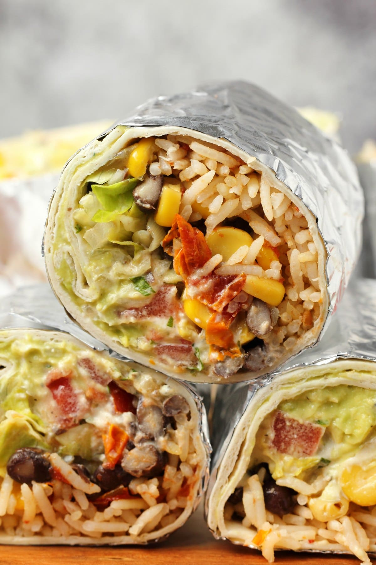 Vegan burrito stuffed with rice, black beans and corn, vegan sour cream and guacamole.