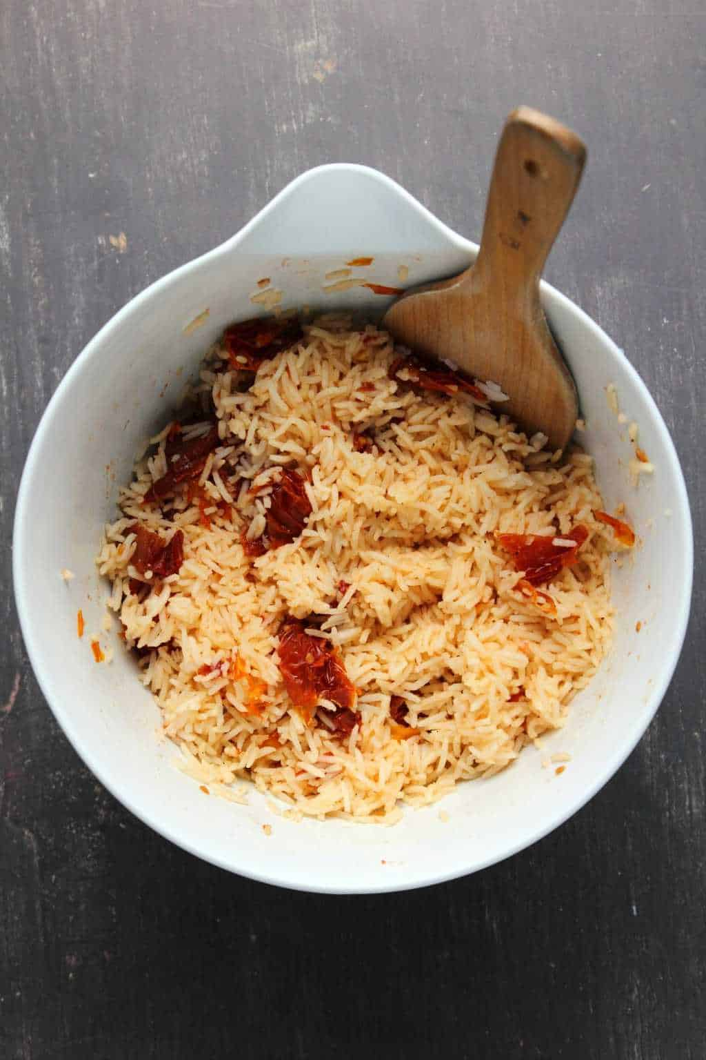 Sundried tomato basmati rice for vegan burritos in a white mixing bowl with a wooden spoon.