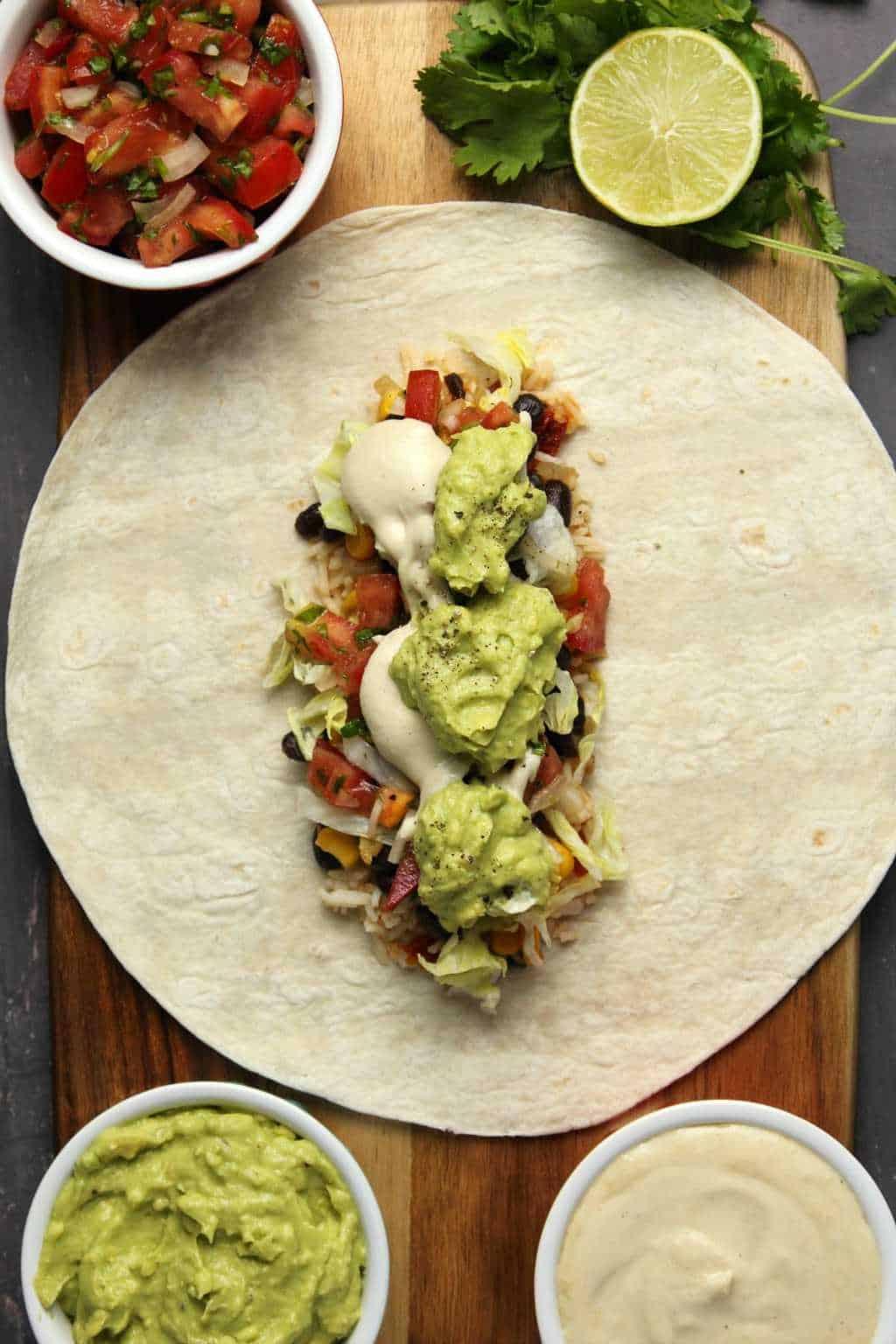 Assembling a vegan burrito on a wooden cutting board.