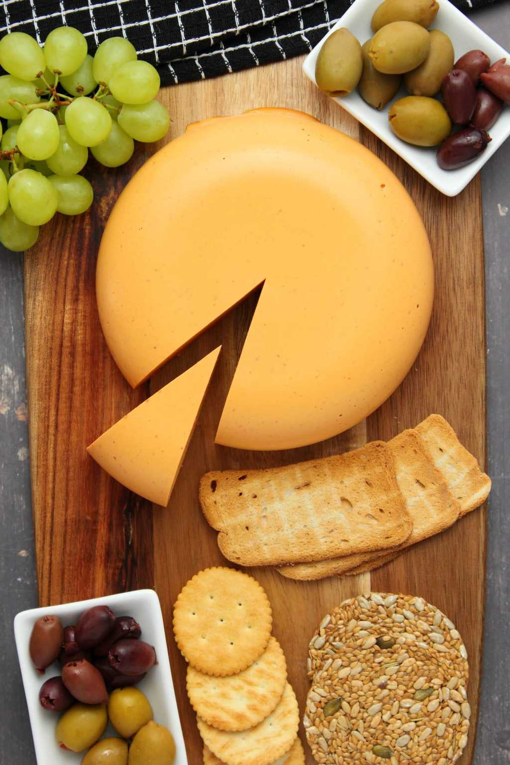 Vegan cheddar cheese on a wooden board with grapes, olives and crackers.