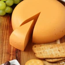 Vegan cheddar cheese on a wooden board with grapes and crackers.