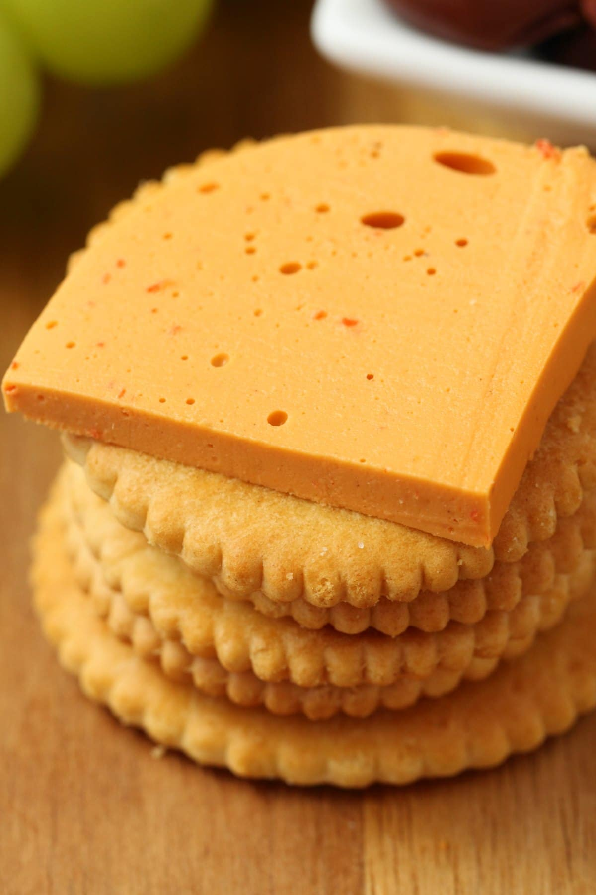 Sliced vegan cheddar cheese on top of a stack of crackers.