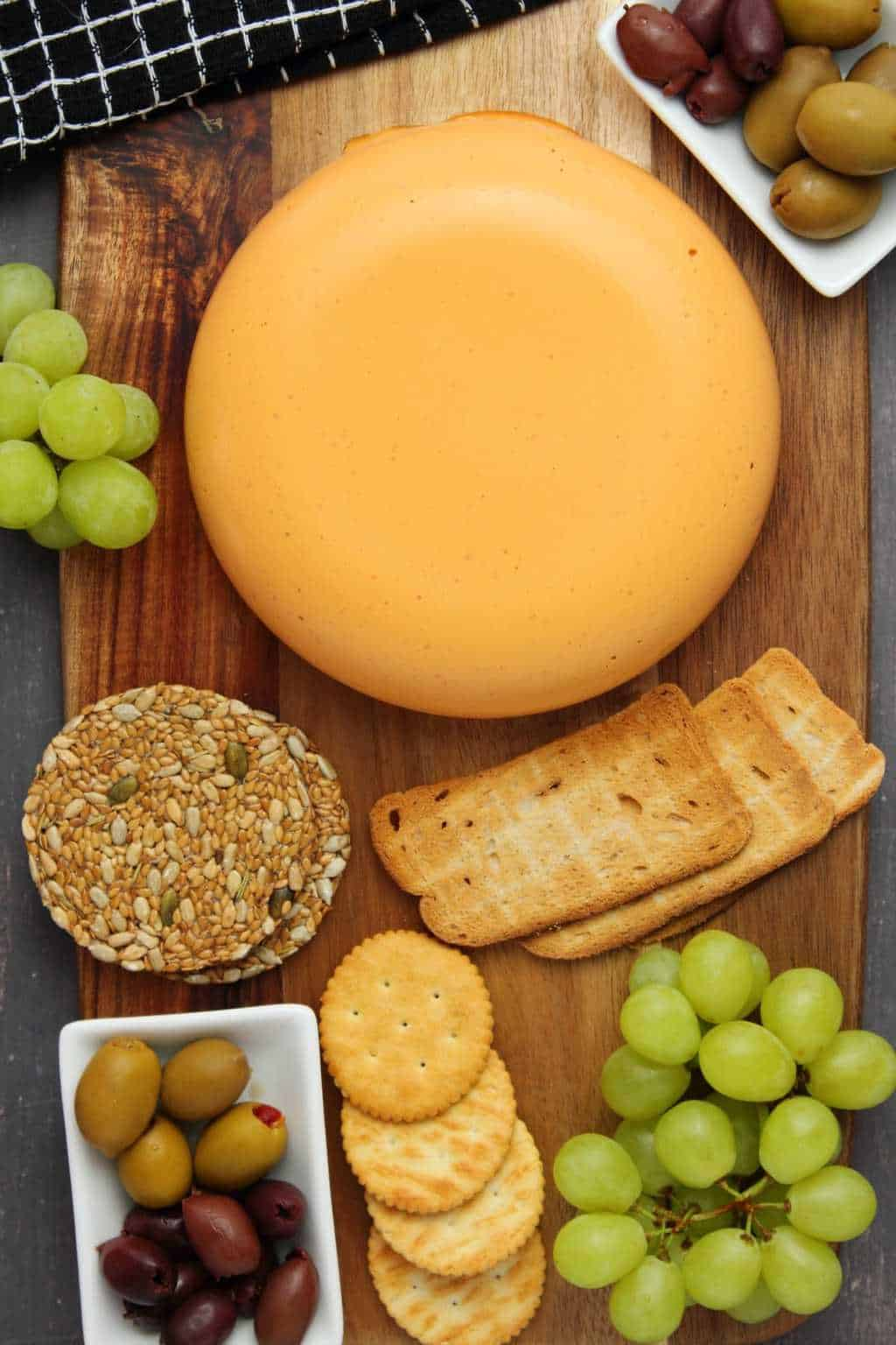 Vegan cheddar cheese round on a cheese board with crackers, olives and grapes.