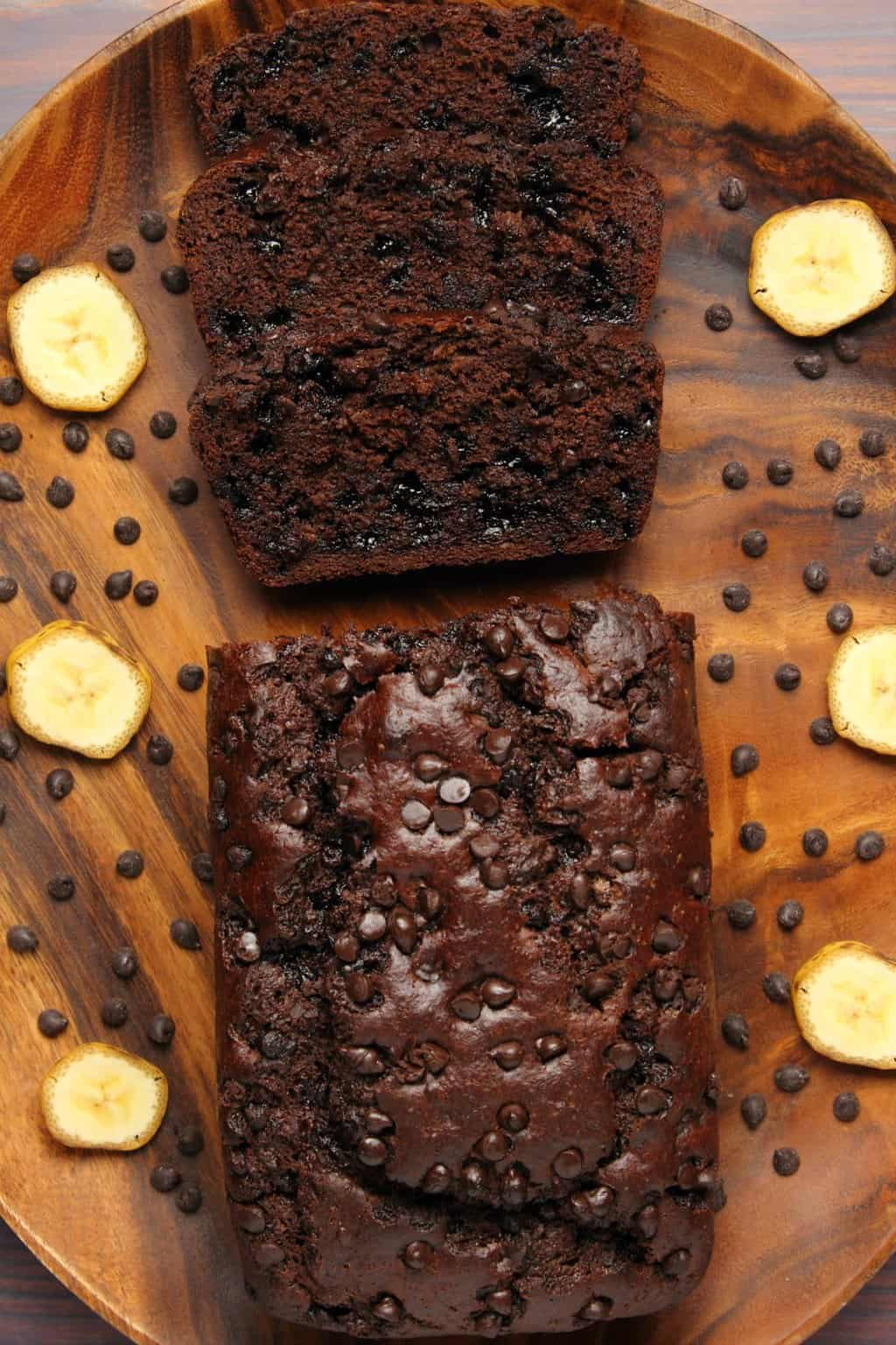 Vegan chocolate banana bread sliced on a wooden plate.