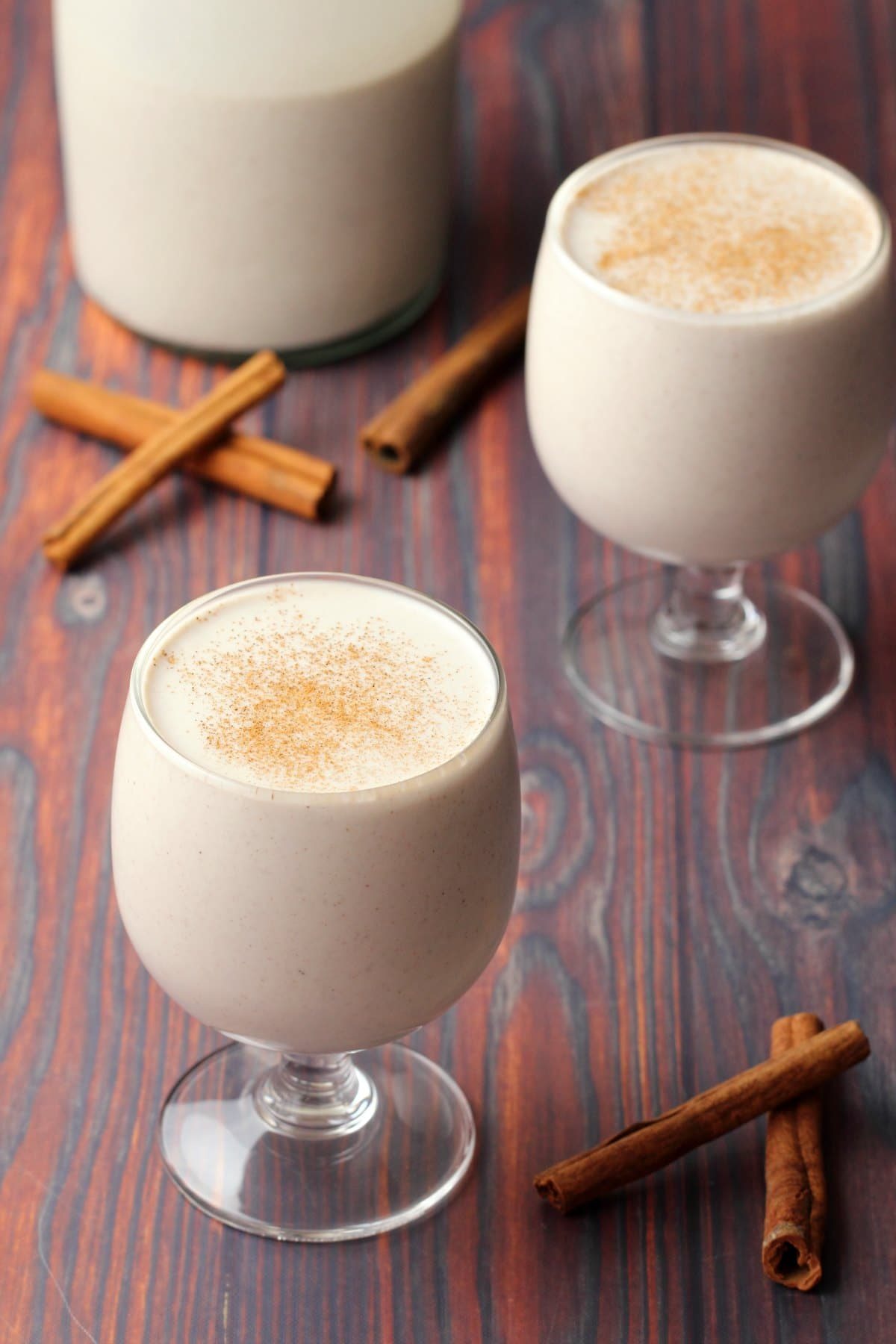 Vegan eggnog in glasses topped with a sprinkle of ground cinnamon.