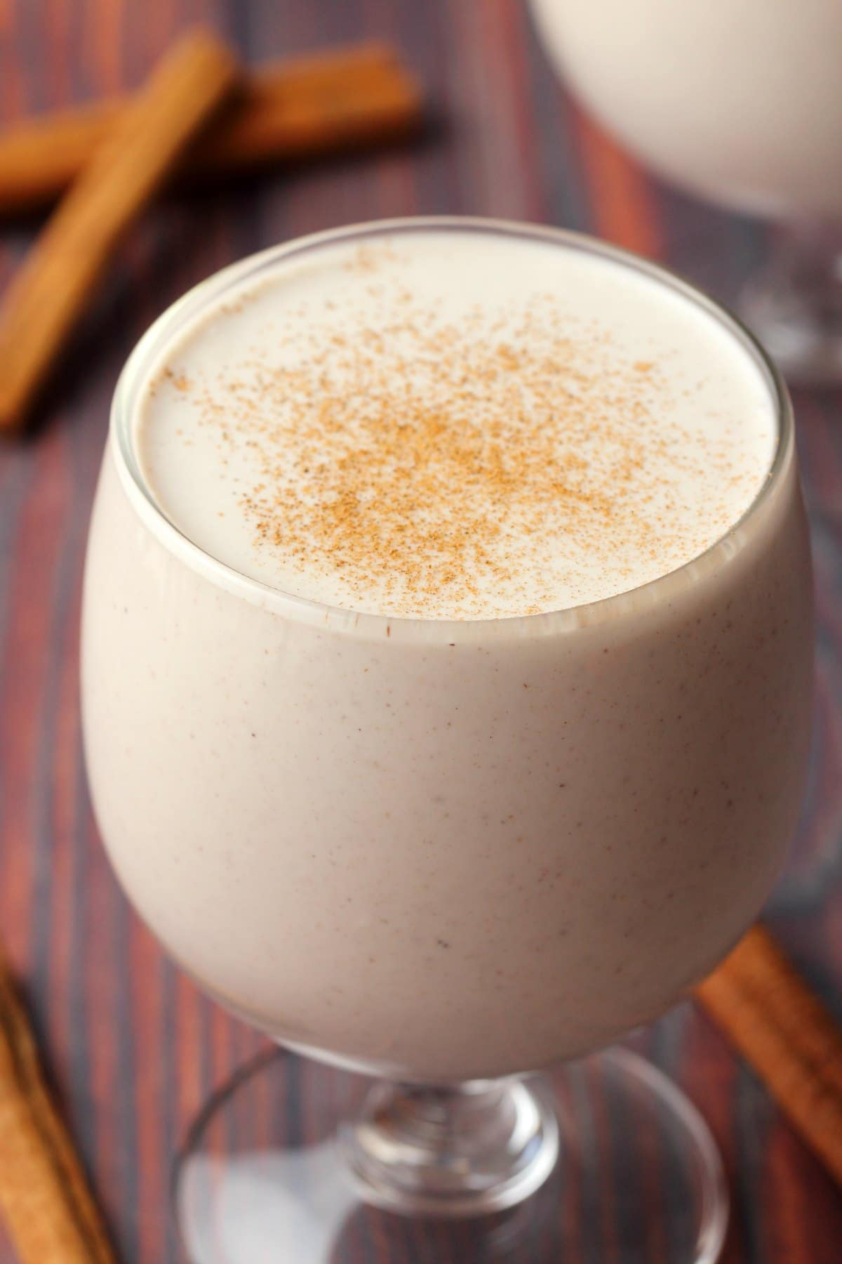 Vegan eggnog in a glass topped with a sprinkle of ground cinnamon.