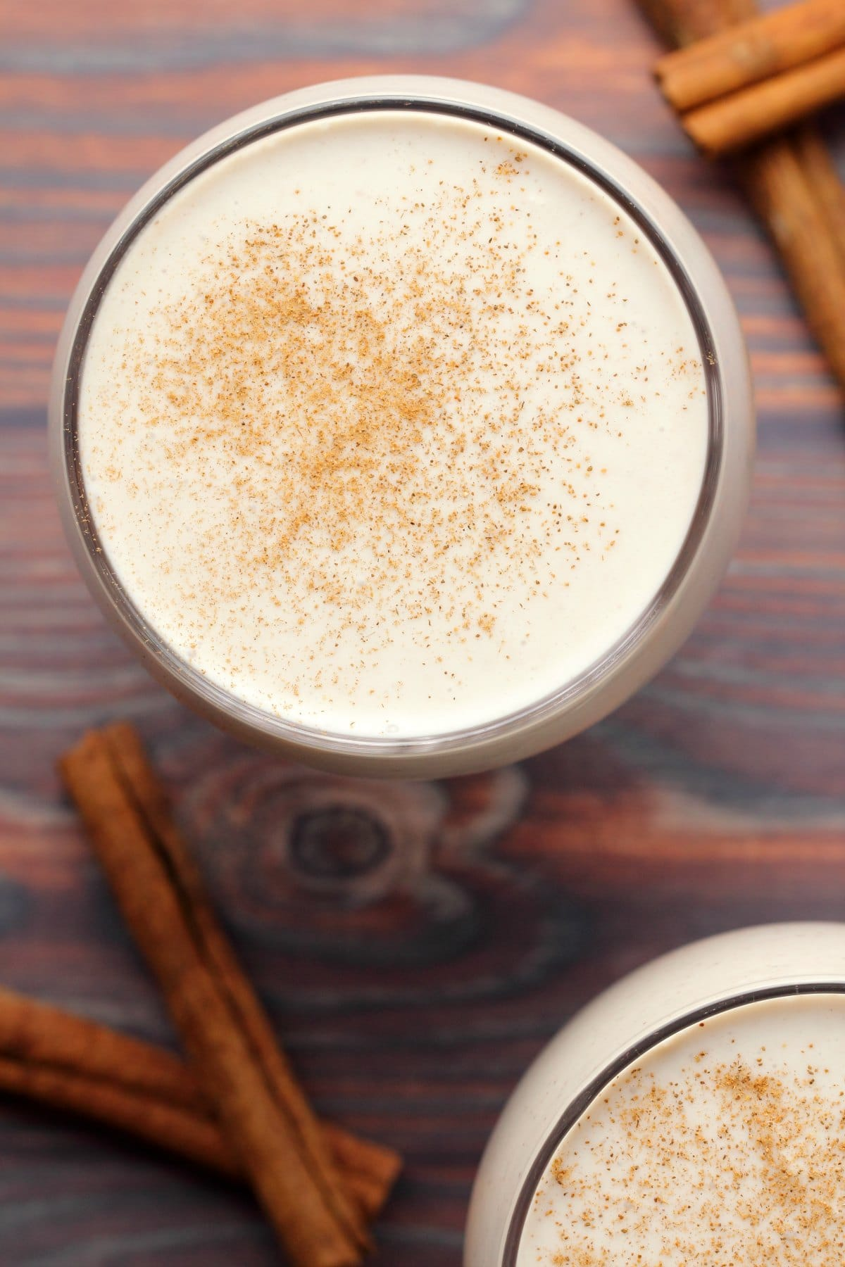 Vegan eggnog topped with a sprinkle of cinnamon in a glass.