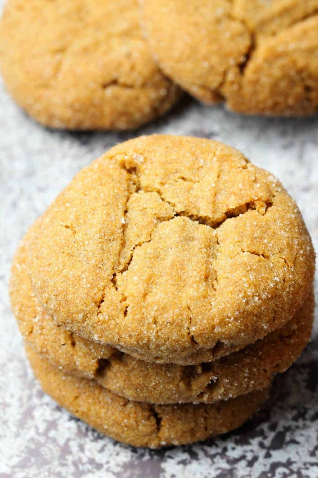 Vegan molasses cookies stacked up on top of each other.