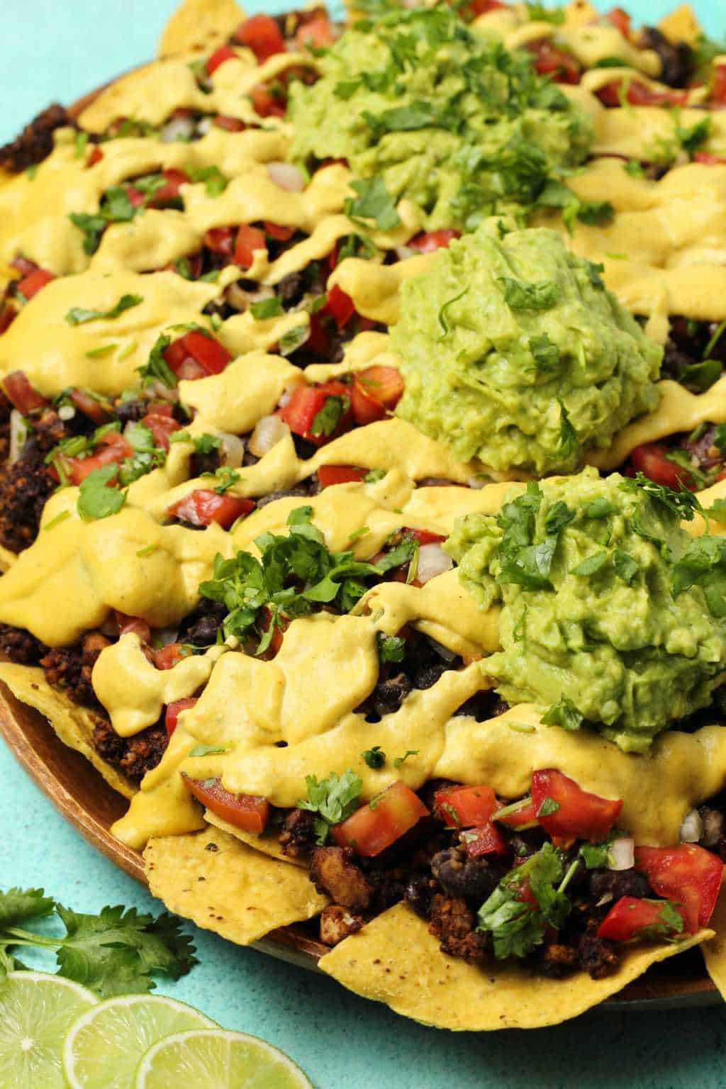 Fully loaded vegan nachos on a wooden platter.