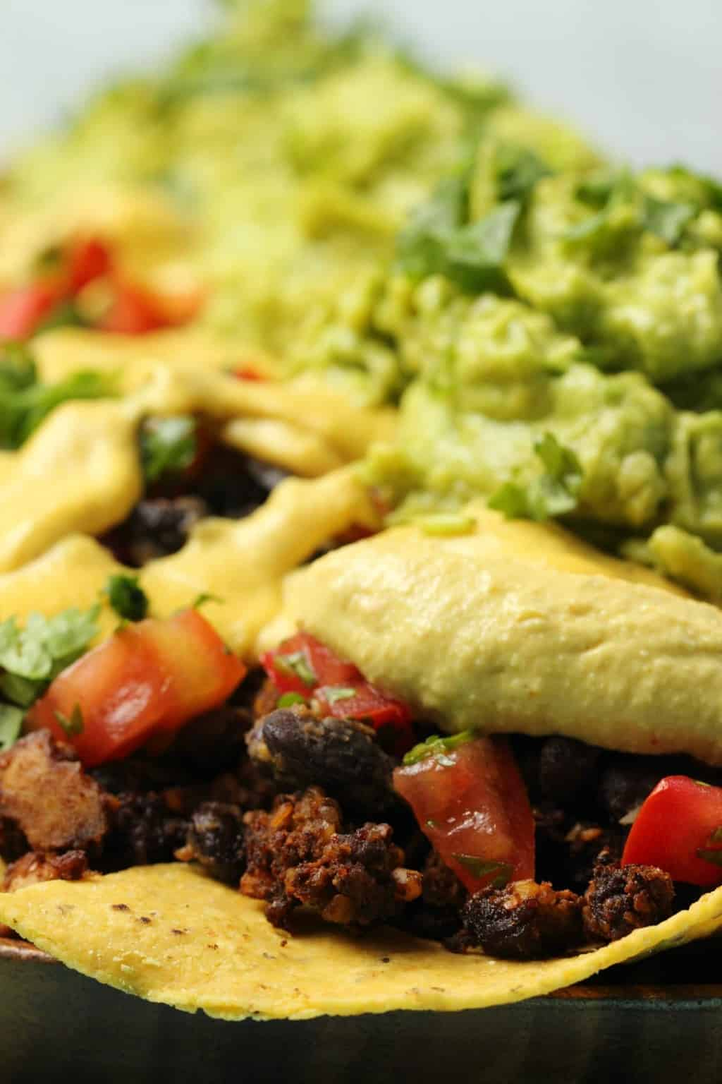 Fully loaded vegan nachos topped with guacamole and cilantro.