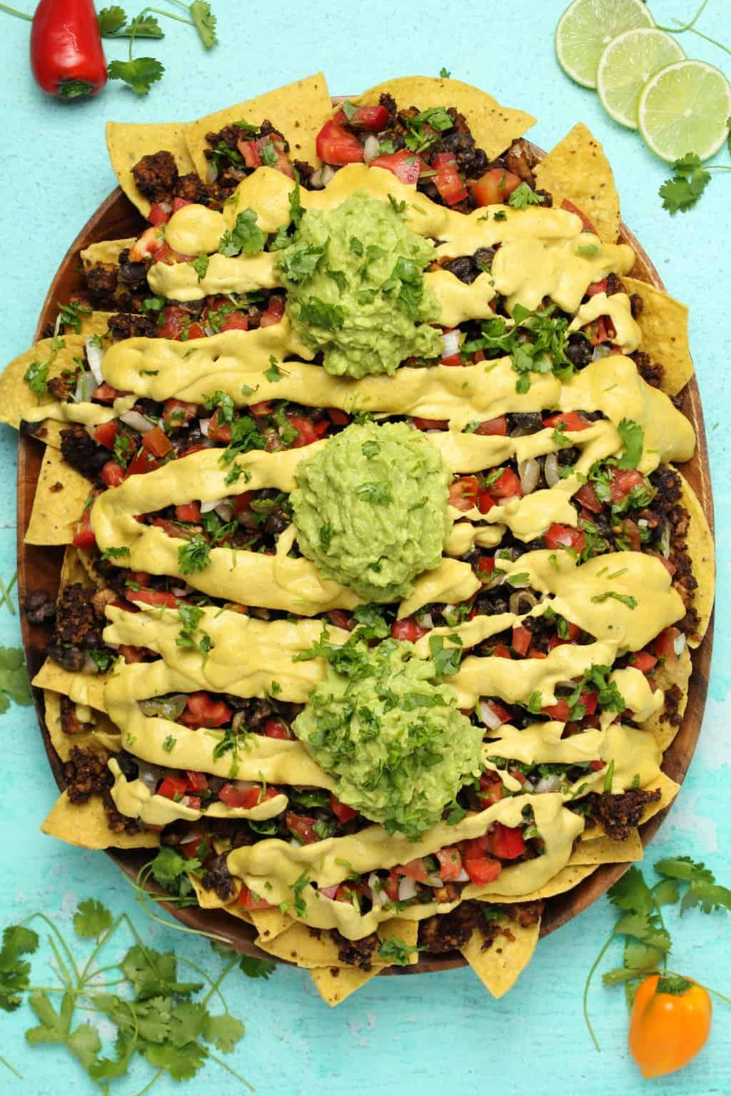 Fully loaded vegan nachos served on a wooden platter.