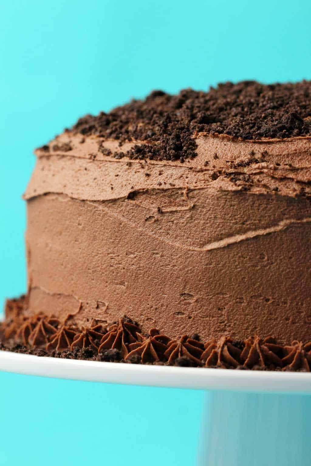 Vegan oreo cake on a white cake stand.