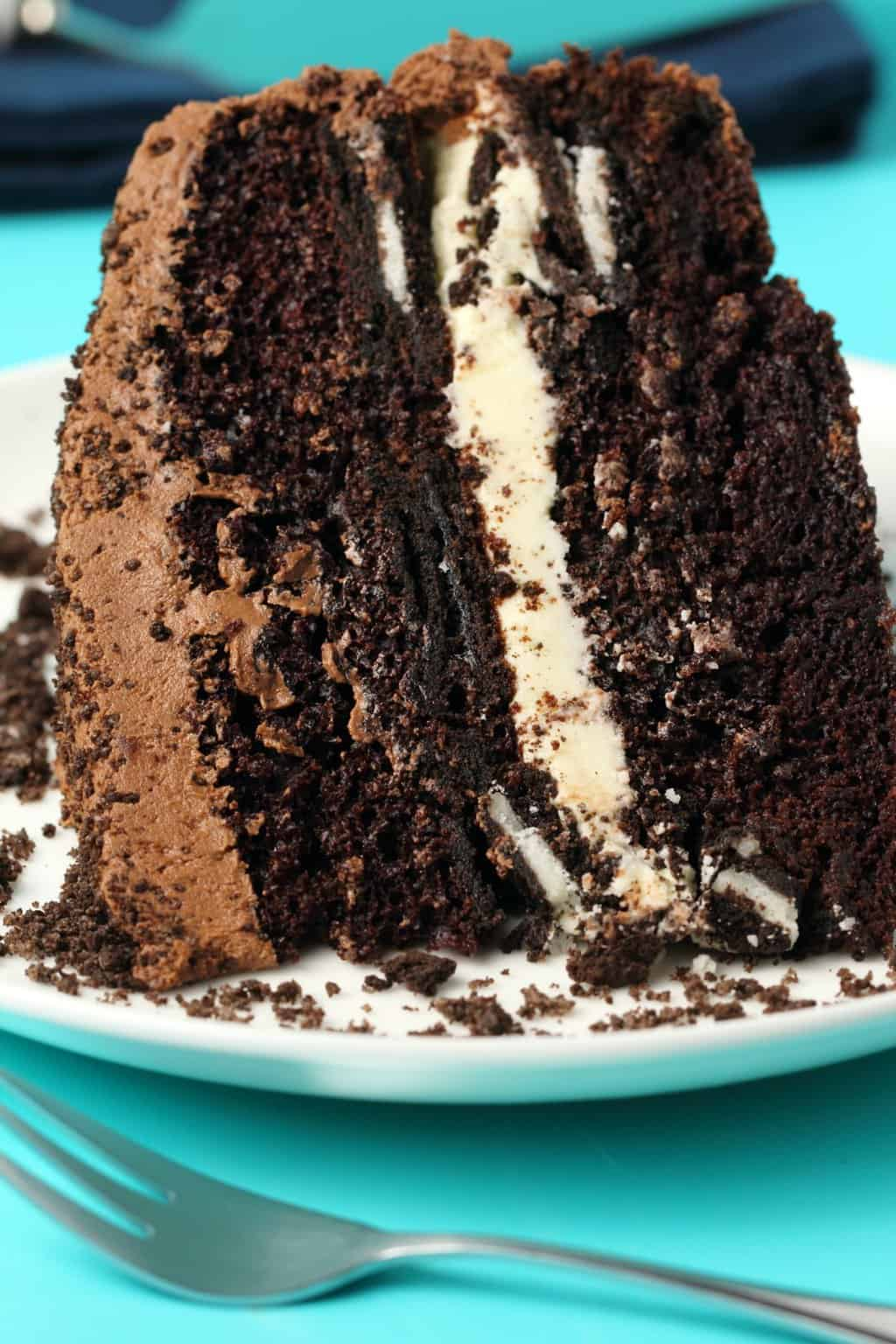 Slice of vegan oreo cake on a white plate with a cake fork.