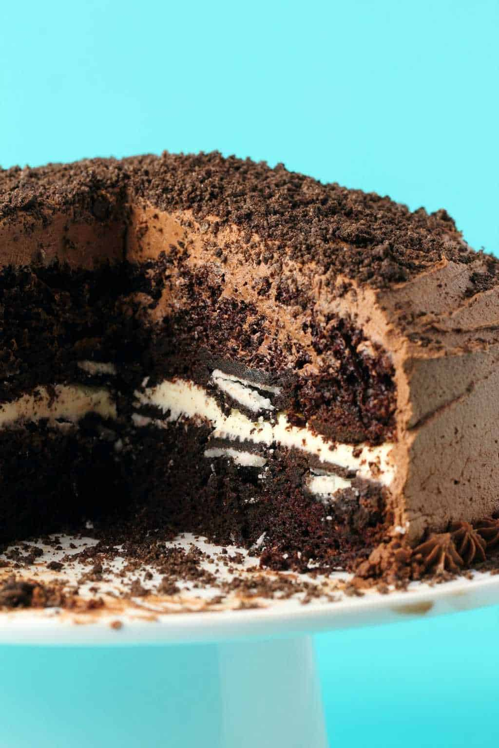 Vegan oreo cake on a white cake stand.