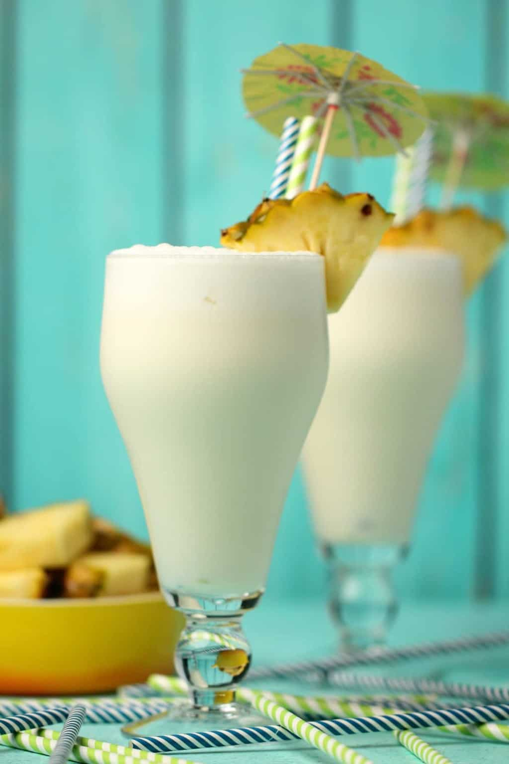 Vegan pina colada in tall glasses with pineapple slices, straws and cocktail umbrellas.