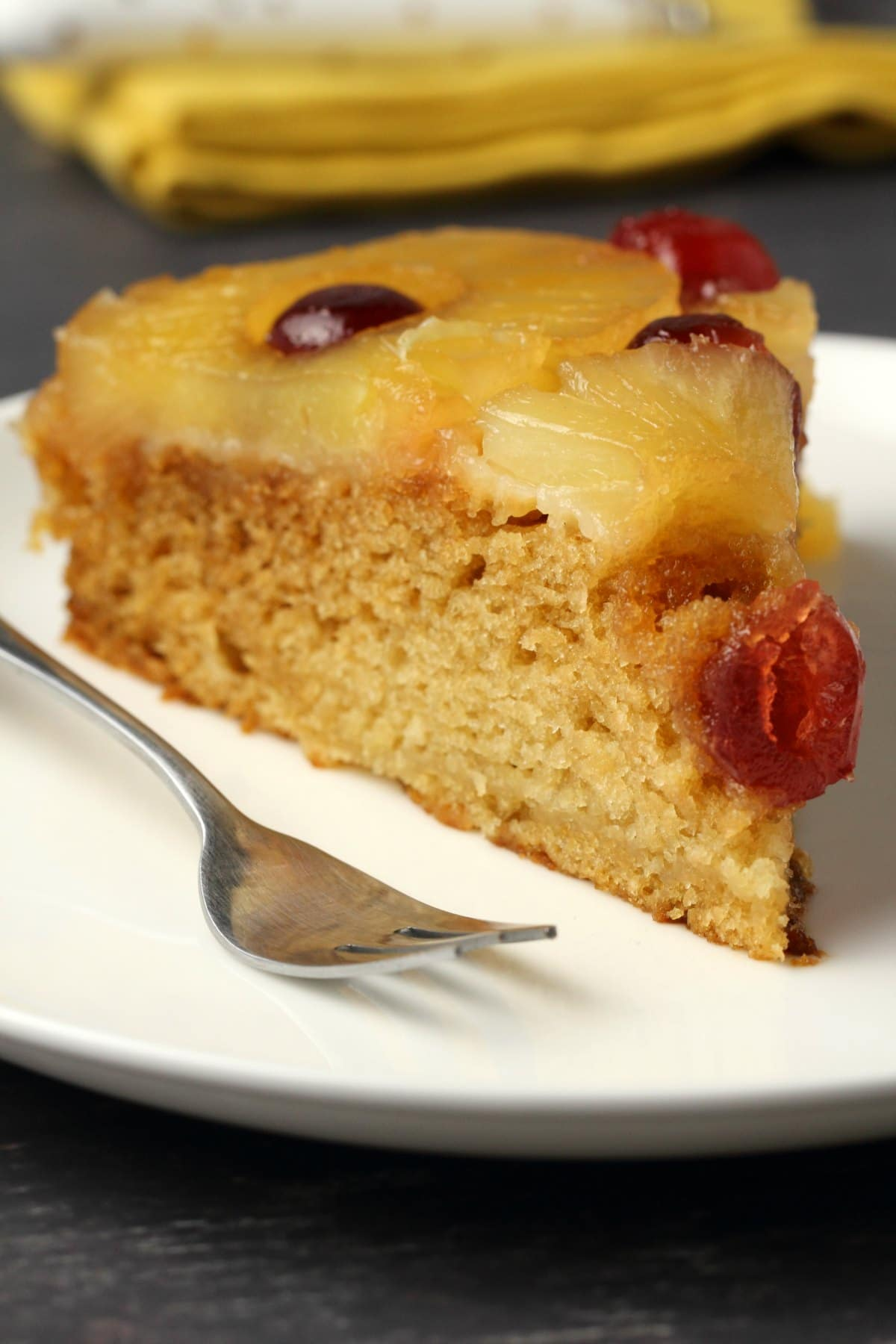A slice of vegan pineapple upside down cake on a white plate with a cake fork.