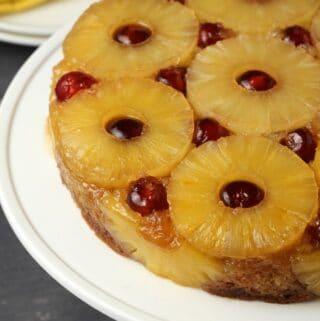 Vegan pineapple upside down cake on a white cake stand.