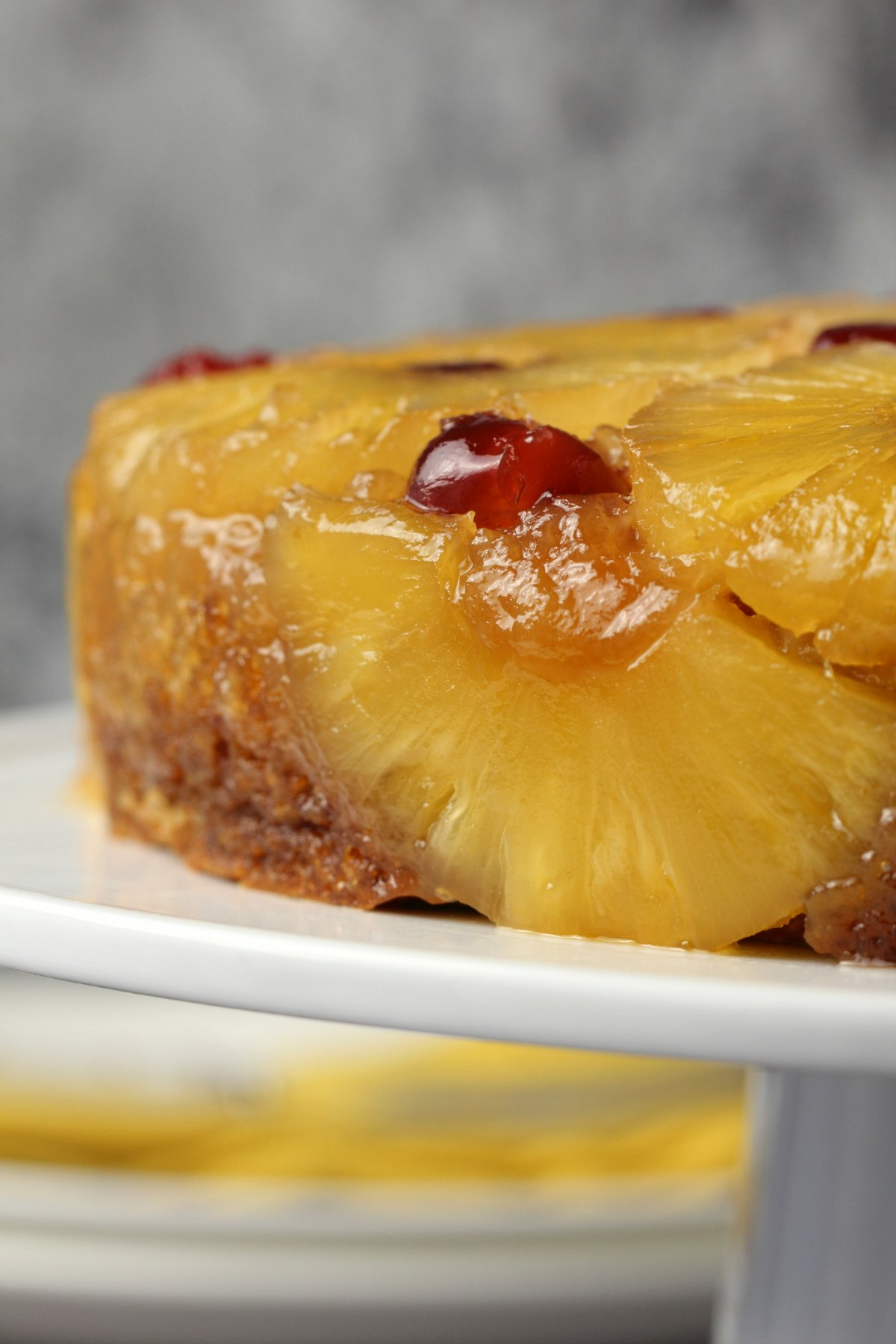 Vegan pineapple upside down cake on a white cake stand.