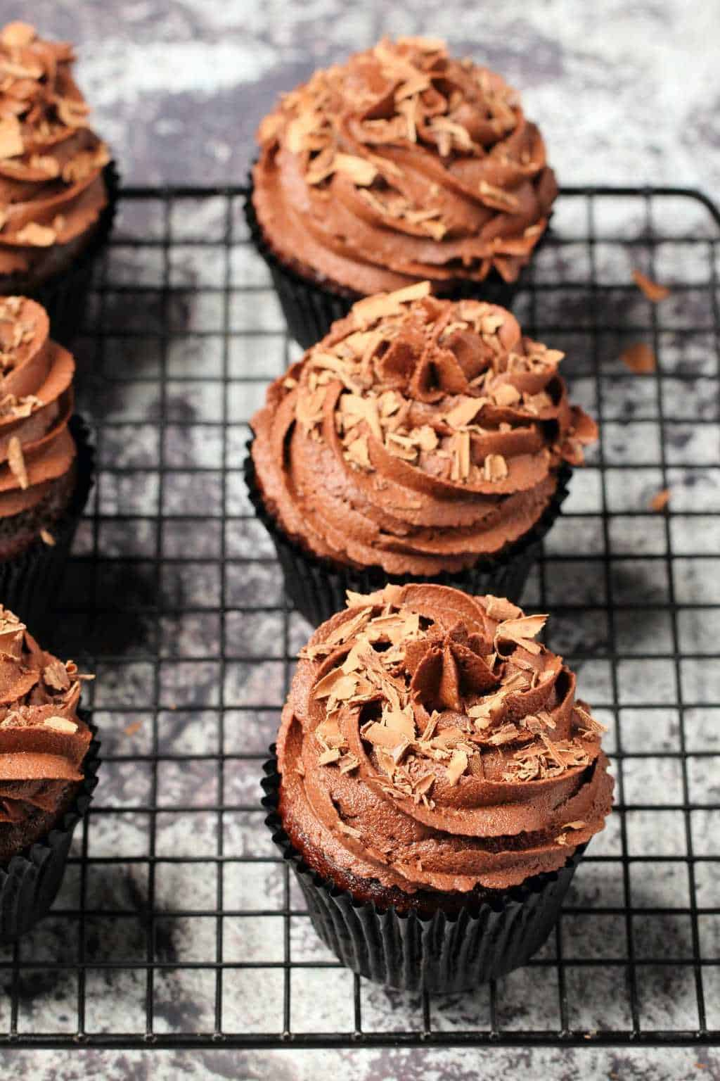 Classic vegan chocolate cupcakes topped with vegan chocolate buttercream and chocolate shavings on a wire cooling rack.