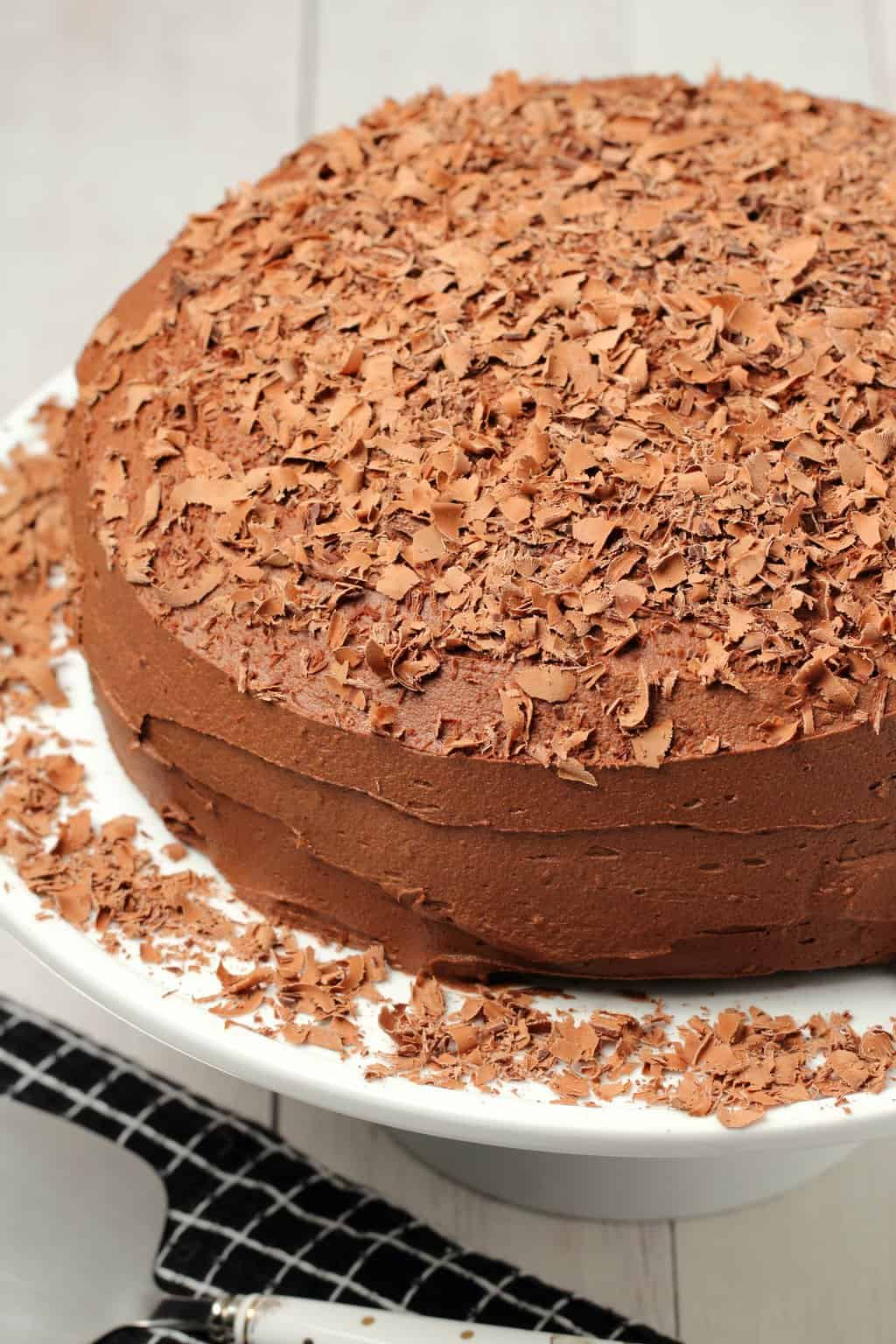 The best vegan chocolate cake topped with chocolate shavings on a white cake stand.