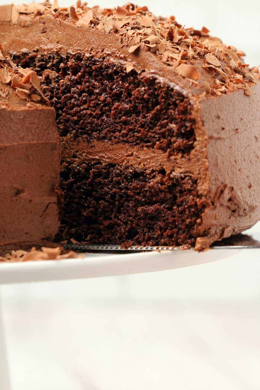 Chocolate cake with one slice cut and ready to serve on a white cake stand.