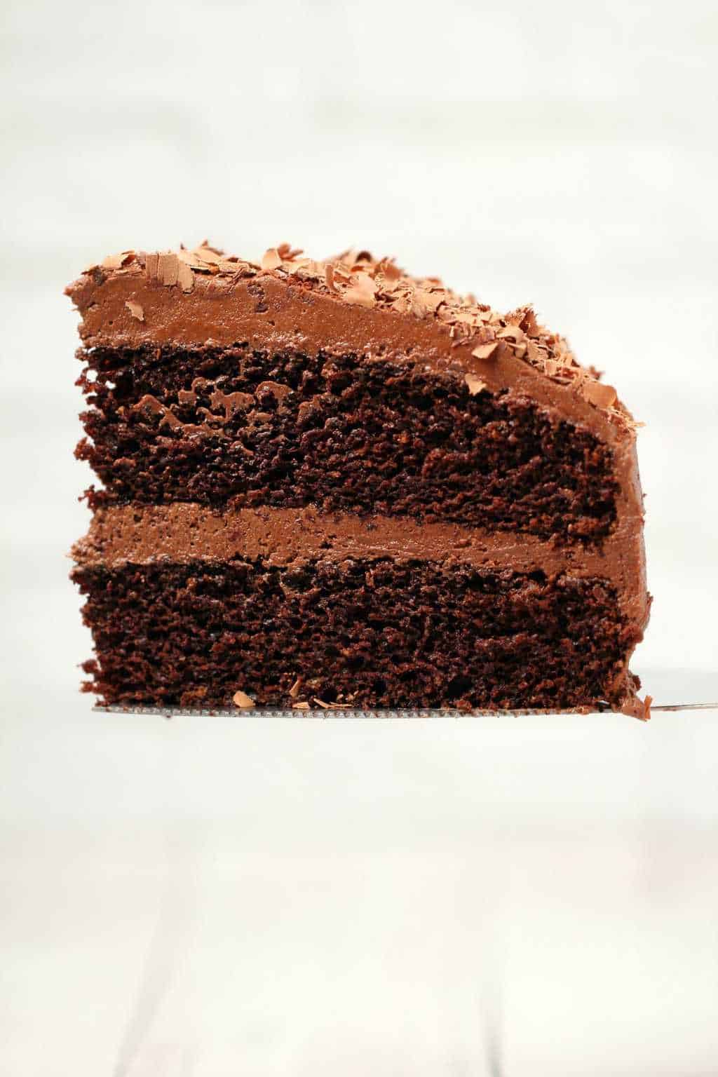 A slice of vegan chocolate cake on a cake lifter.