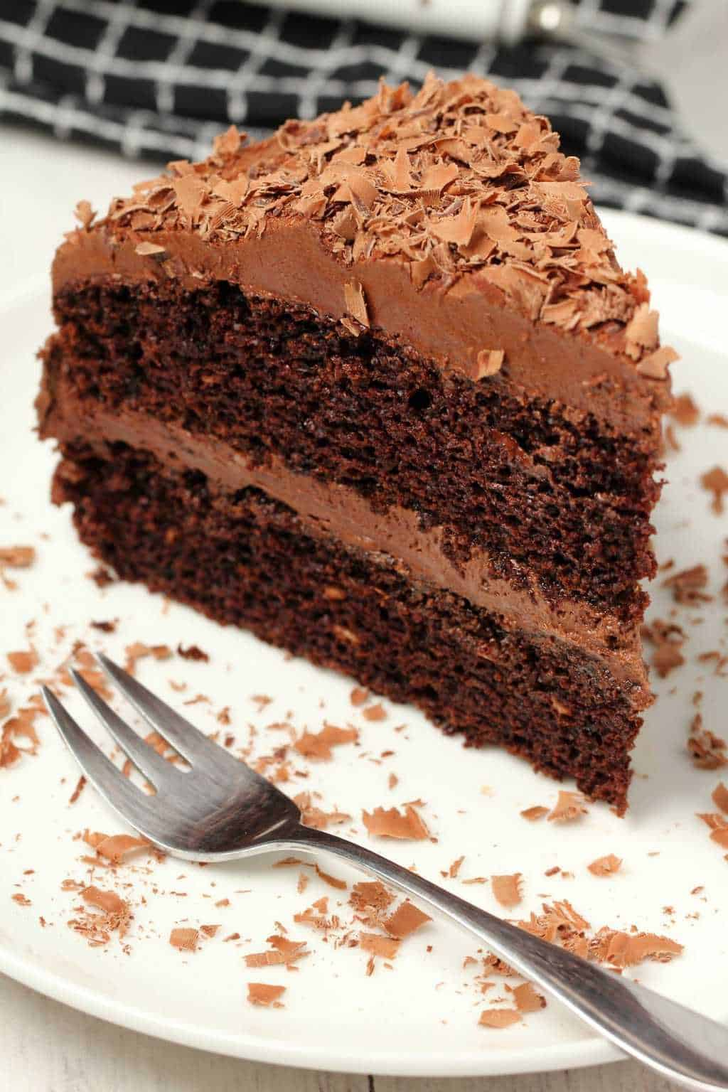 A slice of the chocolate cake on a white plate with a cake fork.