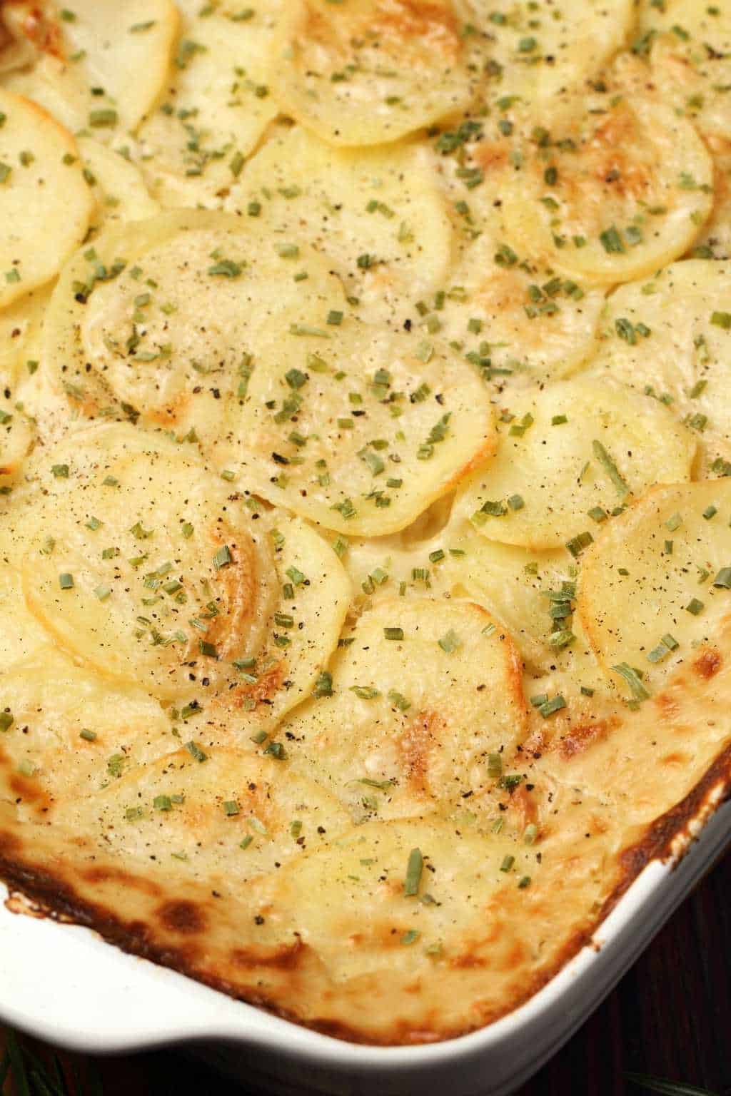 Vegan scalloped potatoes topped with chopped chives in a white dish.