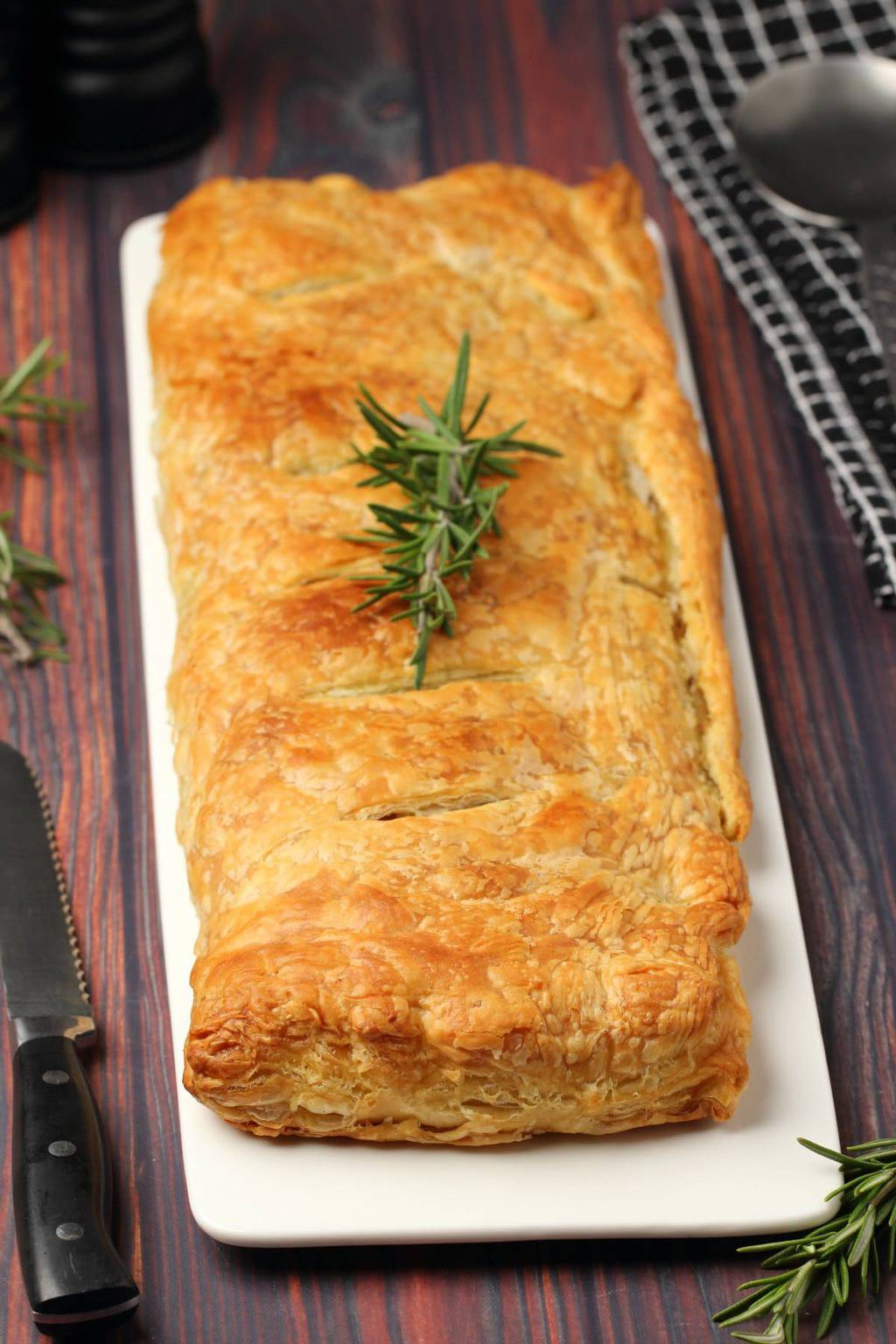 Vegan wellington topped with a sprig of fresh rosemary on a white plate.