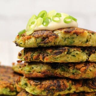 Vegan zucchini fritters in a stack topped with vegan sour cream.