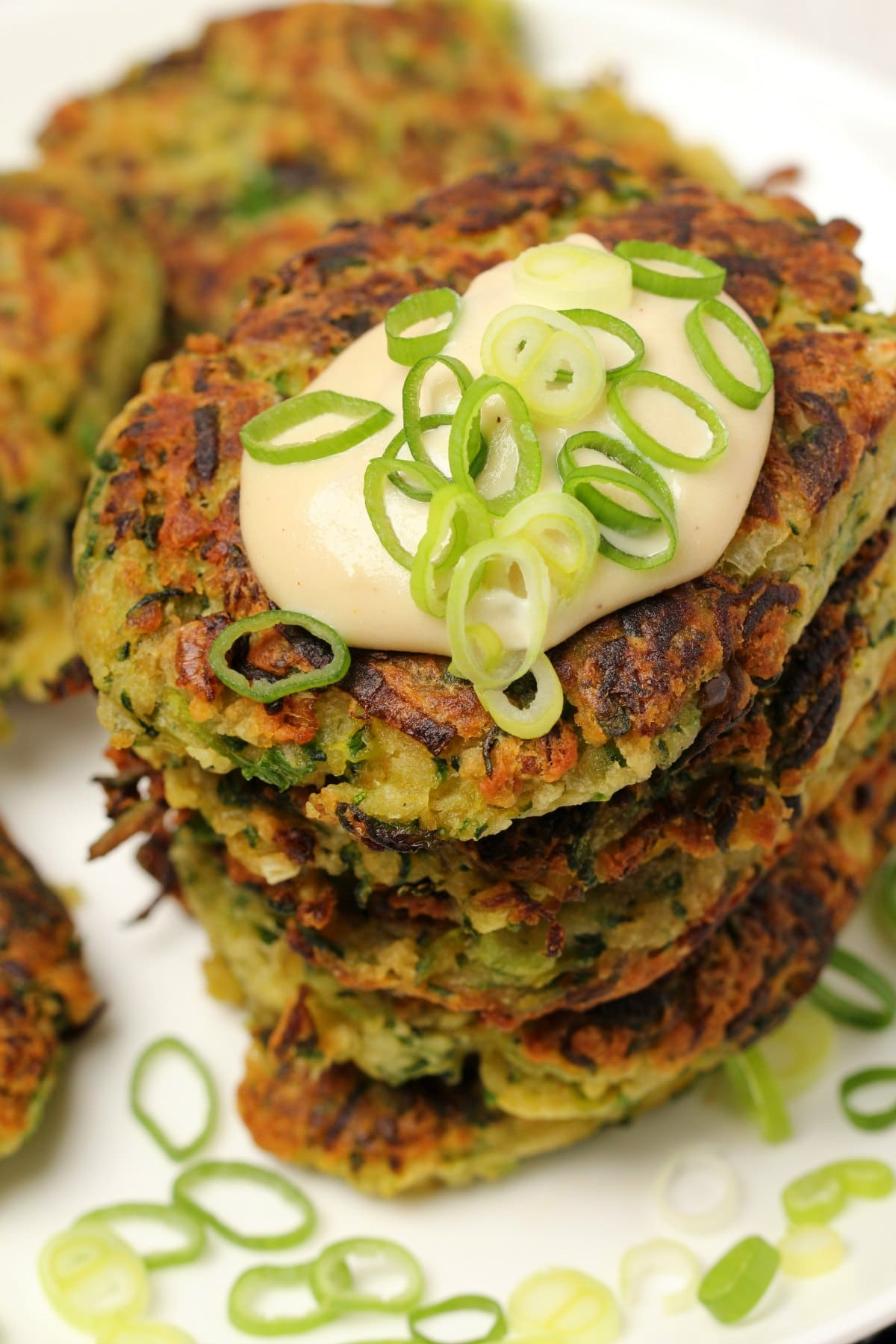 Vegan zucchini fritters topped with vegan sour cream and chopped spring onions on a white plate.