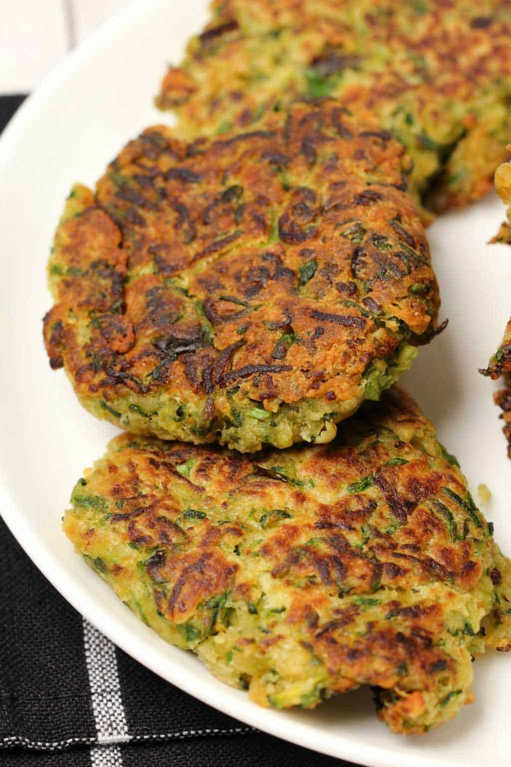 Vegan zucchini fritters on a white plate.