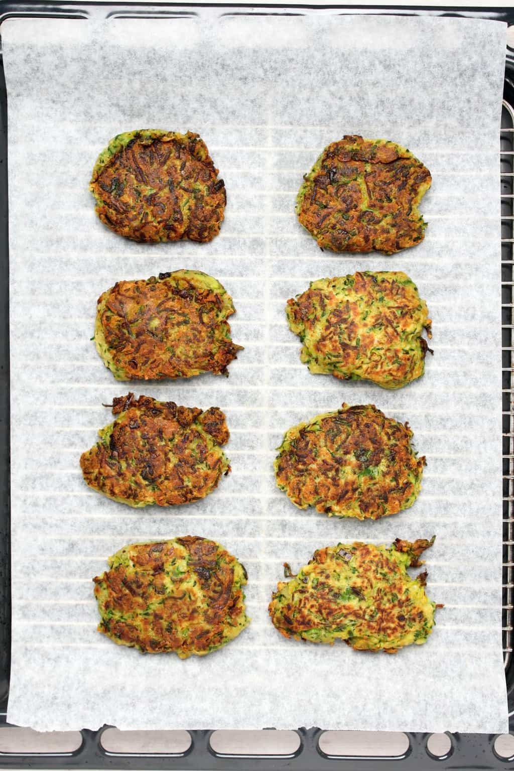 Vegan zucchini fritters on a parchment lined oven tray.