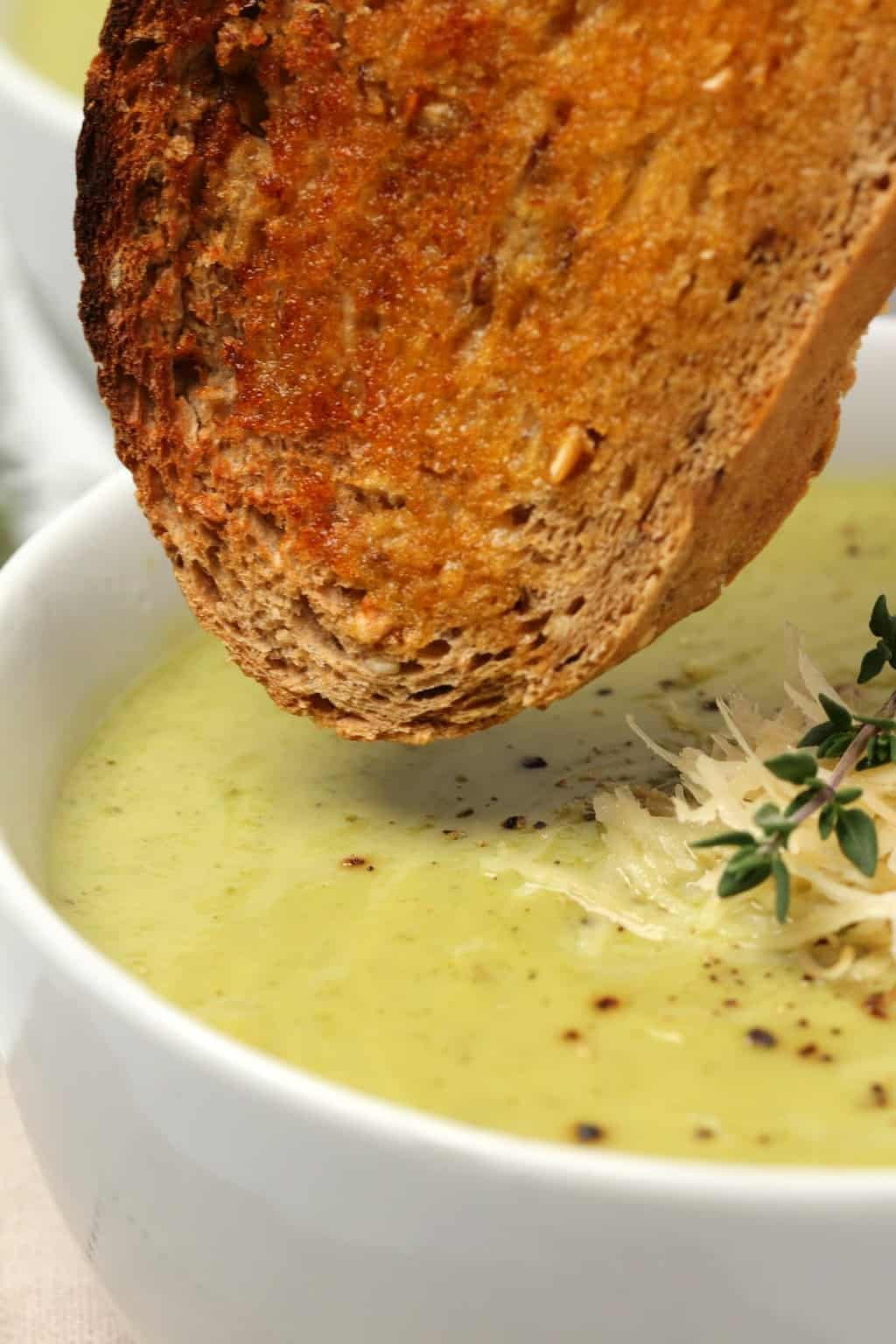 Vegan zucchini soup topped with vegan parmesan and a sprig of fresh thyme in a white bowl with a piece of toasted bread.