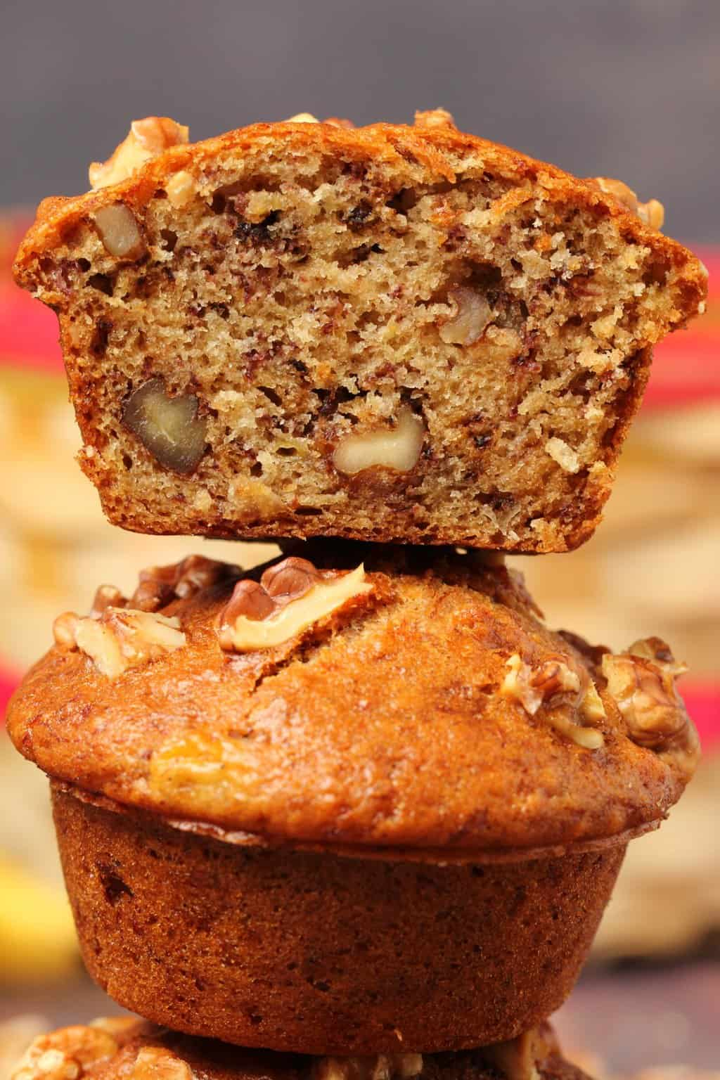 Vegan banana muffins stacked up on top of each other with the top muffin cut in half to show the center.