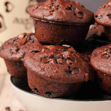 Vegan chocolate muffins stacked up in a white bowl.