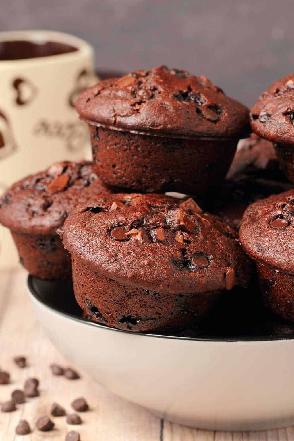Vegan chocolate muffins stacked up in a stone bowl.
