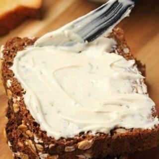 Vegan cream cheese spread on a slice of bread.