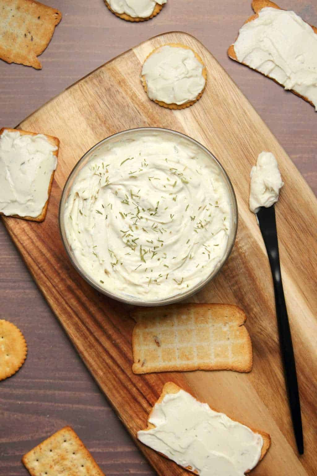 Vegan cream cheese in a glass dish surrounded by crackers.